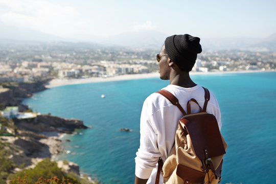 Back view of fashionable young male backpacker meditating on top of mountain, admiring beautiful nature around him. Unrecognizable dark-skinned male looking at blue ocean from birds eye view