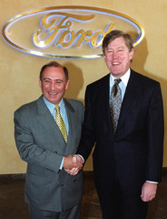 Ford manager James D. Donaldson 54, of Scotland (L) shakes hands in front of a company logo of car m..