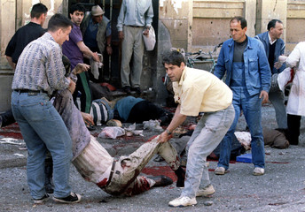 Dead and wounded people lie outside of a Sarajevo indoor market after a mortar shell exploded outsid..