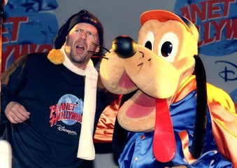 US actor Bruce Willis performs live on stage with a cartoon character during the opening ceremony of..