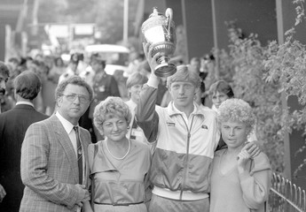 BECKER OF GERMANY POSES WITH TROPHY AND FAMILY AT WIMBLEDON, LONDON.