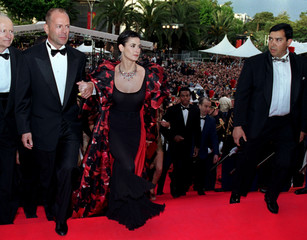 U.S. actor Bruce Willis (L) arrives with his wife Demi Moore (2nd L) under the watchful eyes of a bo..