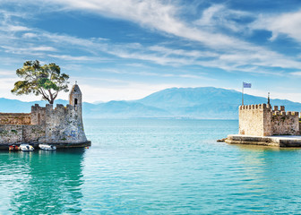 Amazing morning scenery of old port gate in Nafpaktos town, Western Greece, nearby Patras city. Beautiful dramatic blue sky at background. Turquoise water of Ionian sea. Vintage style scenery.