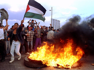 Young Palestinians waves flags and chant slogans around burning tires, during a protest at the borde..