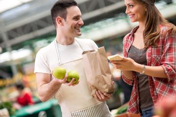 salesman and young woman looking at market.