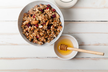 Morning granola with dried fruits, honey, milk and berries on white wooden background. Top view with copy space