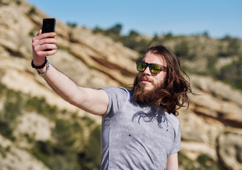 Young man taking selfie photo on the mountains