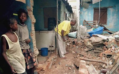 Two girls take a break from helping their father clean up the debris from their bombed house in the ..