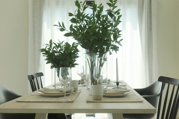 Simply dining table with vase of green leaves at the center