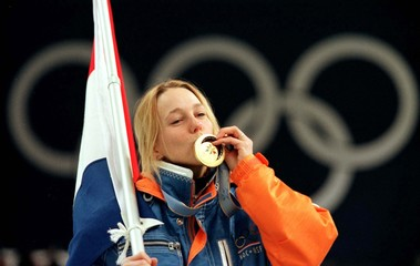 Marianne Timmer of the Netherlands kisses her gold medal as she carries her country's flag after win..