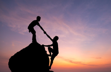 Teamwork couple hiking help each other trust assistance silhouette in mountains, sunset. Teamwork of man to success