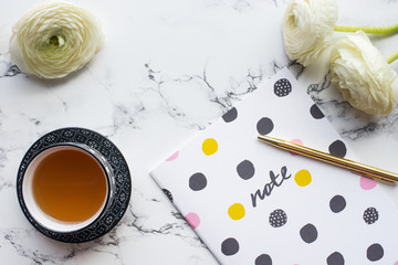 Tea, diary for notes, flowers on marble background, flat lay.
