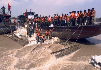 Chinese soldiers try to repair a broken dike to stop floodwaters of the Yangtze River pouring into w..
