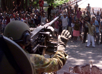 Residents of East Timor's second largest town, Baucau, greet a convoy led by an Australian Army ligh..