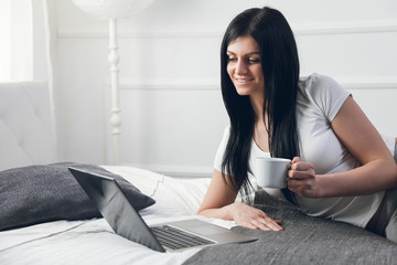Relaxing on the bed. Beautiful woman enjoying a cup of coffee and using her laptop