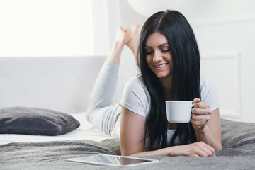 Relaxing on the bed. Beautiful woman enjoying a cup of coffee and using her tablet