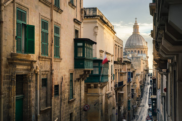 Narrow street of Valletta in the morning with a view of Basilica of Our Lady of Mount Carmel, Malta