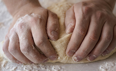 Close-up male hands kneading dough on sprinkled with flour table