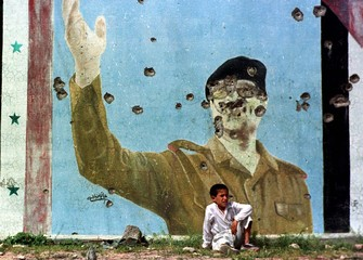 FILE PHOTO APR91- An Iraqi Kurdish boy rests by a bullet riden wall featuring a photo of Iraqi leade..