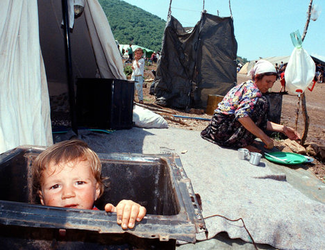 ETHNIC ALBANIAN REFUGEE BABY LOOKS OUT FROM OLD OVEN IN CEGRANE REFUGEE CAMP.
