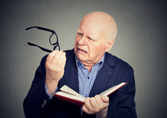 Elderly man holding book, glasses having eyesight problems unable to read