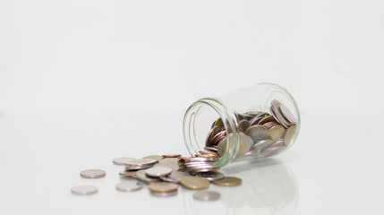 Glass jar saving money with coin on white background.