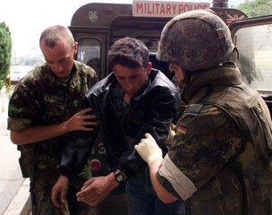 TWO GERMAN NATO SOLDIERS HELP AN ILL ETHNIC ALBANIAN REFUGEE.
