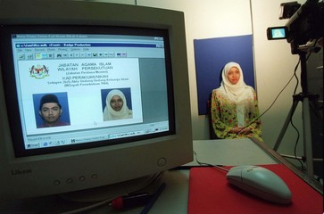 A SOON-TO-BE-MARRIED MALAYSIAN WOMAN GETS HER PICTURE TAKEN FOR THE NEW MARRIAGE CARD.