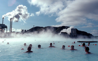 BATHERS IN ICELAND SWIM IN A THERMAL LAGOON.