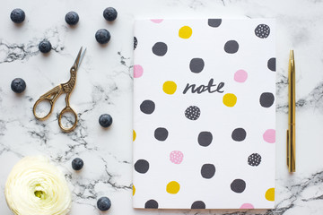 Styled stock feminine desktop with planner, pen, flowers and blueberries on marble background