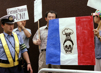 Protestors hold a replica of France's national flag containing the drawing of skull and mushroom clo..