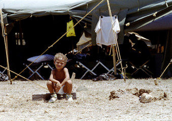A Cuban refugee boy, Darian, 3, from Mariel, Cuba, sits patiently in a diaper waiting for a relative..