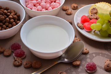 A plate of milk, grapes and crispy balls for breakfast