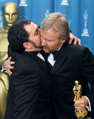 "Director James Cameron (R) hugs producer Jon Landau after their movie ""Titanic"" won best picture Mar.."