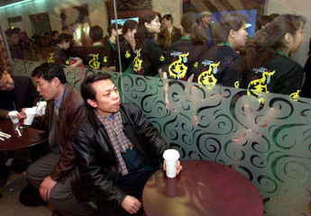 CHINESE TASTE COFFEE AS WAITRESSES READY FOR THE OPENING OF STARBUCKS IN BEIJING.