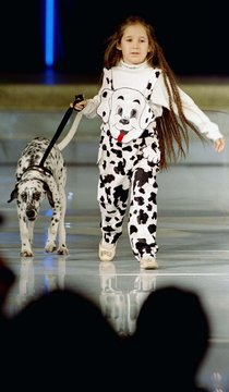 A young girl walks with a Dalmatian dog while showing a child's coat and skirt designed by Bulgarian..