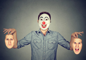 Man in happy clown mask holding two faces expressing anger and sadness