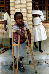 Three little handicapped girls who were saved from Hutu militias by Rwandan rebels stand in a school..