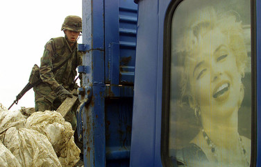 A US Army soldier puts rubbish on a pick-up truck bearing a picture of Marilyn Monroe as US troops c..