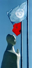 """A statue called """"Love and Peace"""" is silhouetted under the United Nations and Turkish flags June 2 at.."""