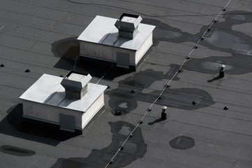 Lines of grey and black asphalt on the flat roof. Cables and devices of ventilation and airing on the top of the building. View from above.