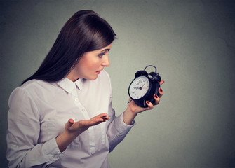 Portrait of upset stressed looking woman with alarm clock