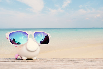 Piggy bank and sunglass on table and sea background, concept save money to travel