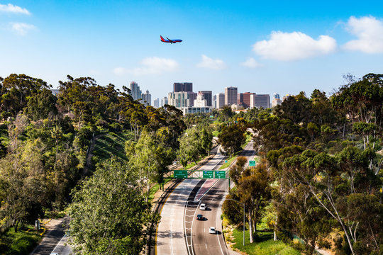 An airplane flies over the Cabrillo Freeway (State Route 163) as it passes through Balboa Park and into the downtown area of San Diego, California.