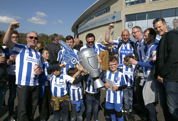 Brighton fans pose for a photograph outside the stadium before the start of the match