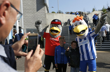Brighton fans pose for a photograph with the club mascots outside the stadium before the start of the match