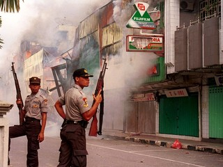 INDONESIAN POLICE CARRYING RIFLES GUARD A BURNING SHOPPING AREA IN THE INDONESIA TOWN OF AMBON.