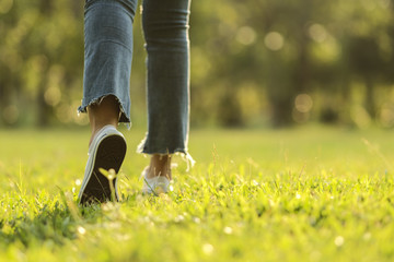 white sneaker jeans walking on green grass with sunset light