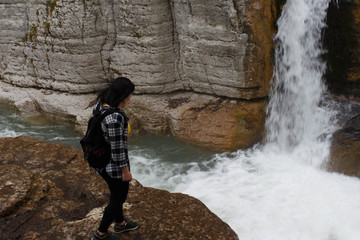 Traveler girl walking in waterfall canyon. Travel adventure and hiking activity, active and healthy lifestyle