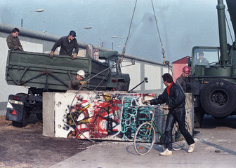 East German workers remove concrete parts of the Berlin Wall and load them onto trucks at the border crossing point at Potsdam Platz